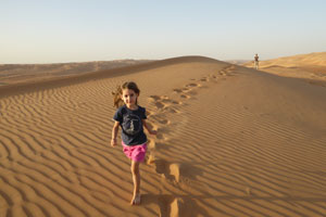 A happy child running on a dune of the Wahiba desert.