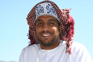 A smiling Omani dressed in the traditional dishdasha and kuma.